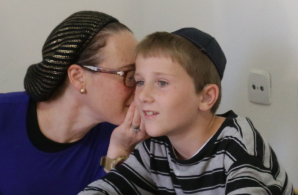 ילד עם לקות שמיעה מקשיב לסוד